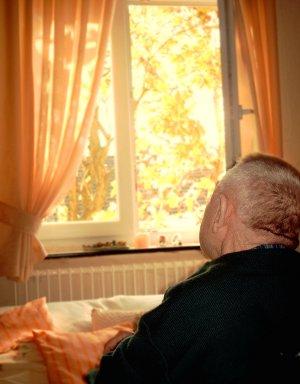 Älterer Mann am offenen Fenster