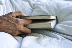 Hand mit Bibel im Bett