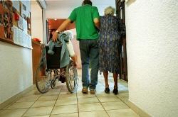 Pfleger mit Seniorinnen im Krankenhausflur