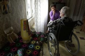 Alte Frau im Rollstuhl am Fenster in abgedunkeltem Raum, mit Tochter