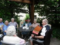 Gemütliche Runde mit Ziehharmonika-Spieler